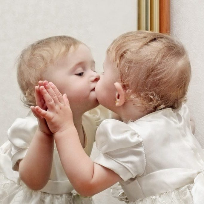 Cute Baby Kissing a Mirror with oneself Reflection